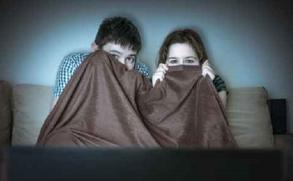 Young scared couple is watching horror on TV. Pair is covering w_209717